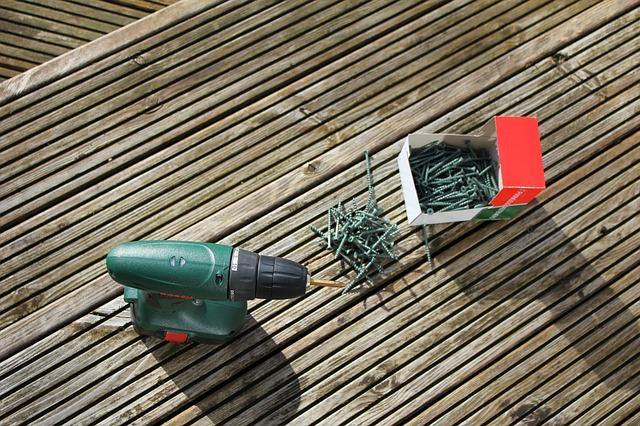 Skruvdragare och spik på ett trädäck